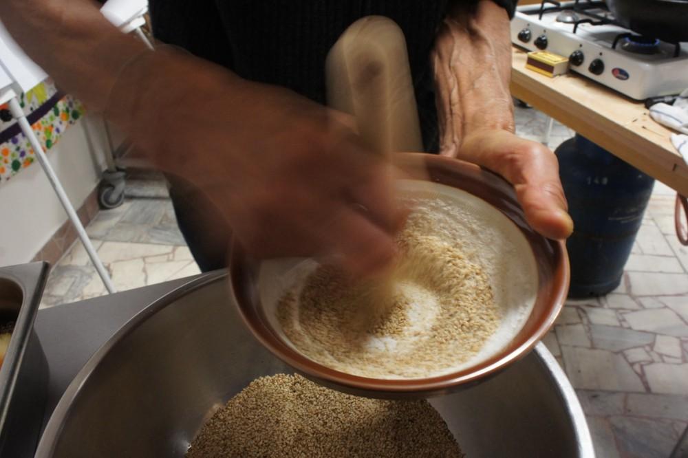 28. Príprava ochucovadla Gomashio (GOMA = sézam, SHIO = soľ) je dôležitá. Používa sa na ochutenie obilniny – uvarenej ryže. Pri servírovaní ryže sa lyžičkou vytvorí jamka, do ktorej sa nasype asi 1 čajová lyžička Gomashia. Je veľmi liečivé. Postup: - sézam namočíme asi na 30 minút do vody – najlepšie na sitku (voda pomôže lepšie uvoľniť pamäť pri pražení) - vyberieme, necháme odkvapkať - vložíme na rozohriatu panvičku (wok), pohybom vareškou spredu dozadu a zľava doprava opražíme nasucho do stmavnutia (nesmieme pripáliť!). - opražené vyberieme do misky - v špeciálnej keramickej miske – mažiariku (Suribashi) krúživým pohybom rozdrvíme morskú soľ (1 PL) na veľmi jemný prášok - pridáme 14 PL opraženého sézamu a krúživým pohybom rozdrvíme na jemno – soľ obalí rozdrvené sézamové zrnká (= lepšie účinky pre organizmus).